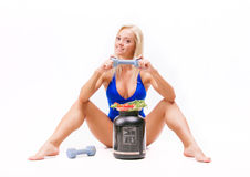 Sports girl with salad, a can of a protein and dumbbells Royalty Free Stock Photos