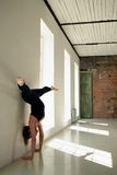 Sports girl stand on hands at wall in yoga position Royalty Free Stock Image