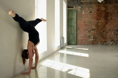 Sports girl stand on hands at wall in yoga position Stock Images