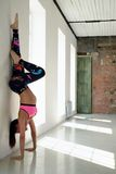 Sports girl stand on hands at wall in yoga position Royalty Free Stock Photography