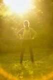 Sports girl in wood in sun beams.  royalty free stock image