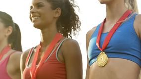 Sports girls smiling, standing with medals on podium, proud of achievements stock image