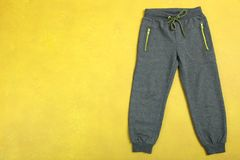 Sports gray pants. For the boy on a yellow background. Copy space Royalty Free Stock Image