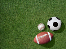 Sports on Green Grass Sports Turf. View  of sports equipment including baseball, soccer and football on grass background Royalty Free Stock Photo