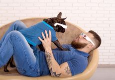 Sports guy in 3D glasses with his dog lying on the couch. look at each other royalty free stock photos
