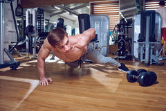 Sports guy does push-ups from the floor on one hand in  gym Royalty Free Stock Photography