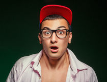 Sports guy with glasses wearing a cap and shirt shows surprise Royalty Free Stock Photography