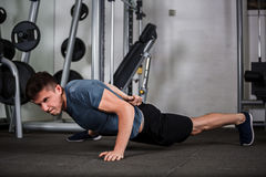 Sports guy push-ups in the gym. Sports guy push-ups on the one hand in the gym Stock Photography