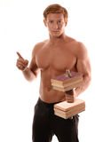Sports guy without a shirt with  dumbbell made of books. Royalty Free Stock Photo