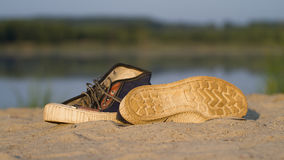 Sports gym shoes on a sand. A pair of sports gym shoes on a sand royalty free stock image