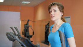 Sports Hall. Girl is training in the gym. An attractive young woman smiles while on a stepper trainer in a fitness room stock video footage