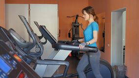 Sports Hall. Girl is training in the gym. Attractive young woman smiling while running on a treadmill in a fitness room stock video footage
