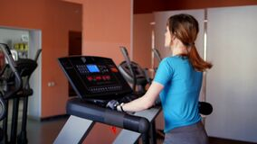 Sports Hall. Girl is training in the gym. Attractive young woman smiling while running on a treadmill in a fitness room. Slow motion stock video