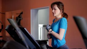 Sports Hall. Girl is training in the gym. Attractive young woman smiling while running on a treadmill in a fitness room. Slow motion stock footage