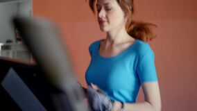 Sports Hall. Girl is training in the gym. Attractive young woman smiling while running on a treadmill in a fitness room. Slow motion stock video footage