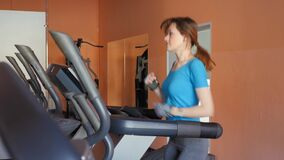 Sports Hall. Girl is training in the gym. Attractive young woman smiling while running on a treadmill in a fitness room stock footage