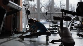 Sports Hall. Girl is training in the gym. Customize an athletic girl with a hairy tail, stretching her legs after exercising in a spacious gym. Beautiful young stock footage