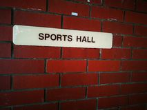 Sports hall sign on brick wall. A photo showing a white sign board with black words saying Sports Hall, on the back ground of a red brick wall. Sport and sports Royalty Free Stock Images