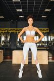 Attractive fitness sports girl in gym. Sports and health. Style and sportswear. Girl in fashionable top and leggings posing in the hall. Fitness model with a stock image