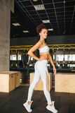 Attractive fitness sports girl in gym. Sports and health. Style and sportswear. Girl in fashionable top and leggings posing in the hall. Fitness model with a stock images
