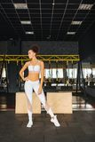Attractive fitness sports girl in gym. Sports and healthy lifestyle. Style and sportswear. Girl in fashionable top and leggings posing in the hall. Fitness model stock images