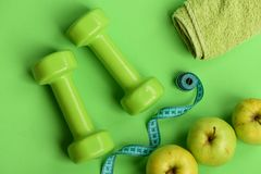 Sports and healthy regime equipment, topview. Dumbbells in green color. Sports and healthy regime equipment, top view. Dumbbells in bright green color, measure Stock Photos