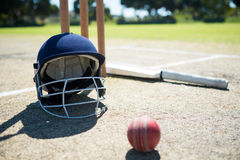 Sports helmet and ball with bat by stumps on pitch Royalty Free Stock Images