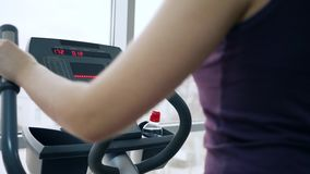 Sports hobby, woman is engaged in sports simulator in gym against of window. Close-up stock footage