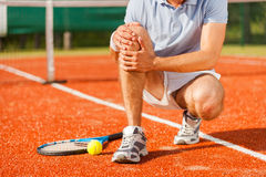 Sports injury. Close-up of tennis player touching his knee while sitting on the tennis court Stock Photo