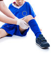 Sports injury. Doctor first aid at thigh of soccer player. Isola. Sports injury. Doctor perform checking and first aid at thigh of youth asian soccer player with Stock Photo