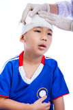Sports injury. Doctor makes a bandage on head patient, on white. Sports injury. Athlete little asian (thai) boy in blue sportswear with trauma of the head royalty free stock photos