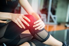 Sports injury at knee in fitness training gym. Training and medical concept. Health care and Sport exercise concept. Pain of body. Part and bone broken theme royalty free stock photography