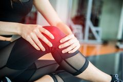 Sports injury at knee in fitness training gym. Training and medical concept. Health care and Sport exercise concept. Pain of body. Part and bone broken theme stock image