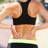 Sports injury - Lower back pain woman holding body. Touching painful waist muscles showing smartwatch on wrist Royalty Free Stock Image