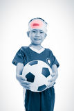 Sports injury. Sad asian boy with trauma of the head holding a f royalty free stock images