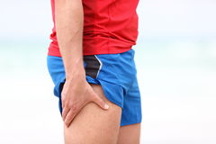 Sports injury - thigh muscle pain. Sports injury. Running muscle stain injury in thigh. Closeup of runner touching leg in muscle pain Stock Photography