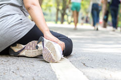 Sports injury. Woman with pain in ankle while jogging Stock Image