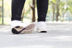 Sports injury. Woman with pain in ankle while jogging. In the park stock photography
