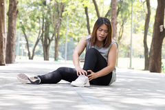 Sports injury. Woman with pain in ankle while jogging. In park stock photos