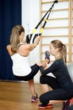 Sports instructor helps to do exercise on suspension rope trx Royalty Free Stock Image