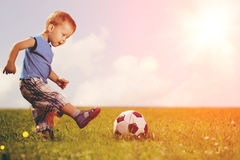 Sports kid. Boy playing football. Baby with ball on sports field