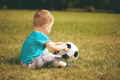 Sports kid. Boy playing football. Baby with ball on sports field Royalty Free Stock Photos