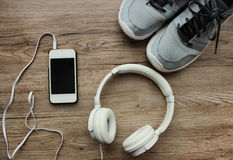 Sports kit for running: large white headphones, mobile phone, running shoes on the wooden background Stock Photography
