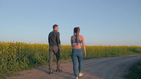 Sports leisure, young couple girl and boy with kanekalon braids and athletic body walking in blooming rapeseed field stock video