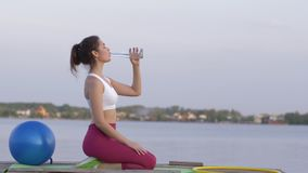 Sports lifestyle, young attractive athletic woman drinks mineral clear water from bottle while doing sports and enjoy. Relax in nature on river against sky stock video