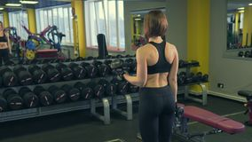 A sports lover lifts dumbbells in front of a mirror, developing musculature. stock video
