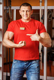 Sports male fitness trainer shows his muscles Royalty Free Stock Image