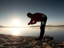 Sports man checking time on his sports watch. Runner at mountain lake exercising Royalty Free Stock Photography
