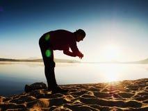 Sports man checking time on his sports watch. Runner at mountain lake exercising Stock Photos