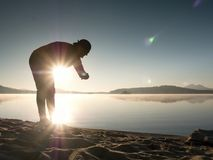 Sports man checking time on his sports watch. Runner at mountain lake exercising Stock Photography